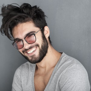 sexy man with beard smiling big against wall